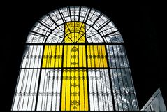 Yellow colored stained glass church window in cross form. Light shining through a yellow colored cross shaped stained glass window and metal works of the church stock photos