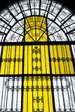 Yellow colored stained glass church window in cross form. Light shining through a yellow colored cross shaped stained glass window and metal works of the church stock photography