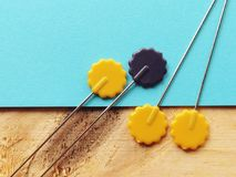 Fancy needle pin. Yellow colors needle pin close up half in turquoise color and wood veneer as a background with natural lights Royalty Free Stock Images