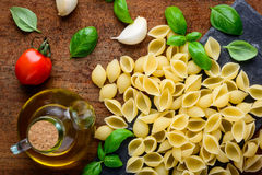 Yellow Conchiglie Rigate Pasta and Cooking Ingredients Royalty Free Stock Photography