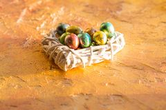 Yellow concrete Background with shiny colorful gold eggs style minimalism.Happy easter card.Quail egg in nest, spring and easter royalty free stock photos