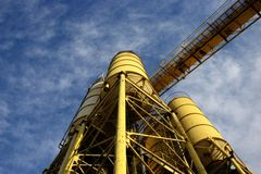 Yellow concrete refinery with blue sky and clouds. Silos yellow giants , viewed from below going to infinity in a blue sky full of clouds Royalty Free Stock Photo