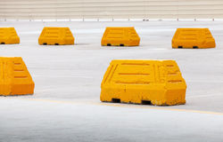 Yellow concrete road barriers on parking area Royalty Free Stock Photos