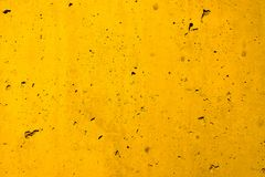Yellow concrete wall coarse facade made of natural cement with holes and imperfections as an empty rustic texture background. Yellow concrete wall coarse facade stock photo
