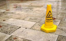 Yellow cone with caution slippery surface sign, on wet pavement tiles.  stock image