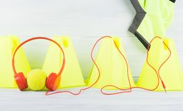Yellow cone fence on grey background and sport t-shirt, behind the tennis ball which is wearing red headphones royalty free stock image