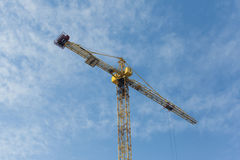 Yellow construction crane on blue sky background. Sunny day, hor Stock Images