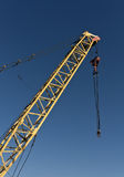 Yellow construction crane and blue sky. Royalty Free Stock Photography