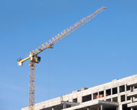 Yellow construction crane on building over blue sk Royalty Free Stock Image