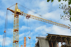 Yellow construction cranes, building metal-concrete structure, green branches of a tree. Horizontal photo. Royalty Free Stock Photography
