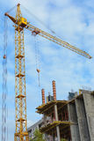 Yellow construction cranes and unfinished building with metal-concrete structure on a background of blue sky with white Royalty Free Stock Photos