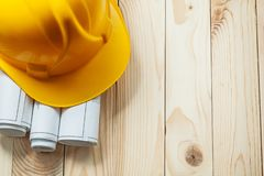 Yellow construction helmet and white rolled blueprints on wooden boards royalty free stock photography