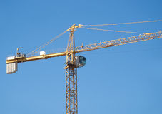 Yellow construction hoisting crane over blue sky Stock Photo