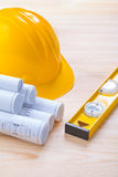 Yellow construction level hardhat and blueprints Stock Images
