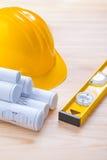 Yellow construction level hardhat and blueprints Stock Images