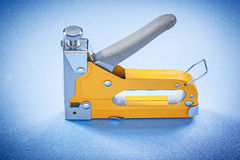 Yellow construction staple on blue background directly above Royalty Free Stock Images
