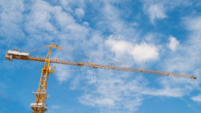 Yellow construction tower crane with blue sky Stock Images