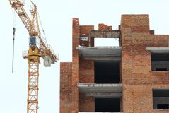 Yellow construction tower crane and unfinished brick multistory building. Isolated Royalty Free Stock Image