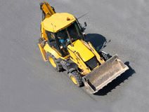 Yellow construction tractor. On road isolated of business vehicles series Royalty Free Stock Image