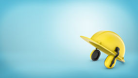 A yellow construction workers hard hat with earmuffs on blue background. Royalty Free Stock Image