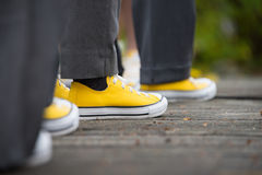 Yellow converse sneakers with grey slacks at a wedding. A line of groomsmen wear yellow converse sneakers while they wait in line during a wedding. The Stock Image