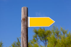 Yellow copyspace arrow sign on wooden pole Royalty Free Stock Image