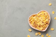 Yellow corn flakes in  heart shaped plate on gray background. I like breakfast cereal. Copy space for text. Yellow corn flakes in  heart shaped plate on gray stock images
