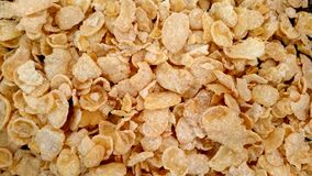 Yellow Corn Flakes scattered on flat surface closeup stock photography