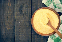Yellow corn flour in a ceramic bowl on a rustic wooden table. In Stock Image