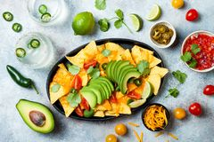 Yellow corn nachos chips with melted cheese sauce, avocado, jalapeno, cilantro leaves, tomato salsa and iced margarita stock image