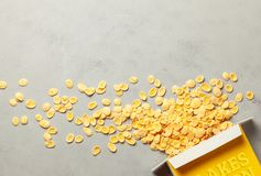Yellow cornflakes scattered out of the package on a gray background. Cereal breakfast. Copy space for text. Yellow cornflakes scattered out of the package on a stock photography