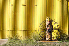 Yellow corrtugated wall background. Yellow corrugated iron wall with old fire extinguisher in front Stock Photography