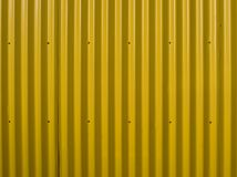 Yellow corrugated wall. Yellow steel background. Mounted with screws. Can be used as a background. Vertical direction royalty free stock images