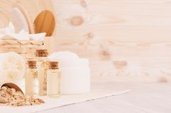 Yellow cosmetics oil, oatmeal cereals and white cream, bath accessories on beige wooden shelf, copy space. Royalty Free Stock Photo
