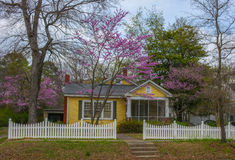 Yellow Cottage with Redbud Tree and Picket Fence Royalty Free Stock Photos