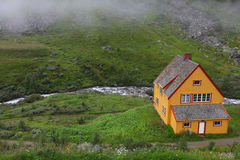 Yellow cottage beside river in the mountains Stock Photo
