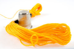 Yellow cotton thread and a thimble Royalty Free Stock Photography