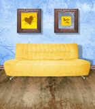 Yellow couch on grunge blue. Yellow couch against grunge blue painted wall and brown wood floor. Digital illustration from my images and designs Royalty Free Stock Photo
