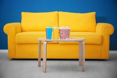 Yellow couch and table with snacks in home cinema. Watching movie royalty free stock photo