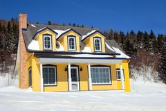 Yellow country house. A typical canadian yellow country house located in the Charlevoix region in Quebec, Canada. It is surrounded by snow, forest and deep blue Stock Image