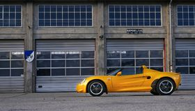 Yellow Coupe Parked Near Brown Painted Warehouse royalty free stock images