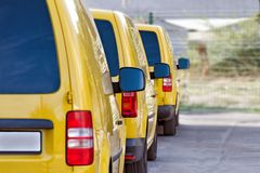 Yellow courier or taxi cars are lined up in parking lot. Stock Photo