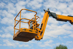 Yellow cradle of the hydraulic lift. Against the blue sky Stock Images