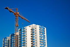 Yellow crane. On a background of blue sky and a fragment of apartment house Royalty Free Stock Images