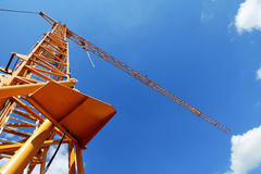Yellow crane against the blue sky Stock Images