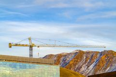 Yellow crane against mountain and blue cloudy sky. Yellow crane behind a building and against a rugged mountain and blue cloudy sky . The crane is used to lift royalty free stock images