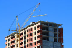 Yellow crane and brick building under construction Stock Photos