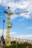 Yellow crane. On construction site against blue sky with beautiful clouds Royalty Free Stock Images