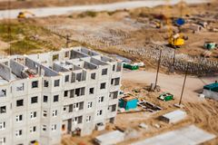 Yellow crane on construction site. Tilt-shift photo royalty free stock images