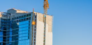 Yellow crane elevator attached to side of building Royalty Free Stock Photography